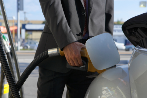 Businessman filling gas into car, close up